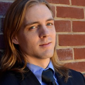 Rob McGinness, Baritone, smiling in formal wear in front of a brick wall.