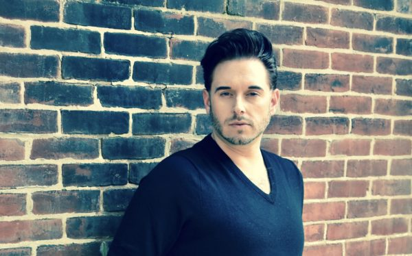 Dominick Chenes, Tenor, leaning against a brick wall.