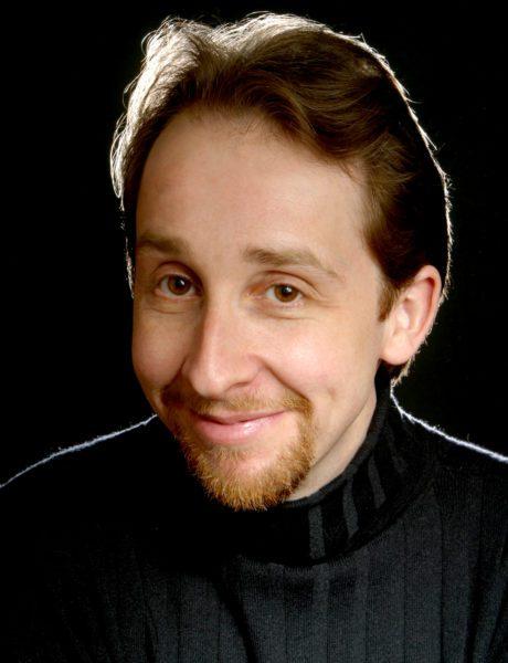 David Kravitz, baritone headshot, dramatically lit with an empty background.